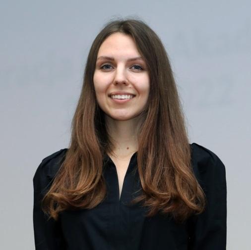 Uśmiechnięta młoda kobieta w długich rozpuszczonych włosach, w czarnej bluzce
